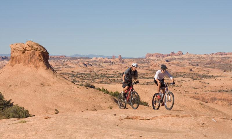 Two guys mountain biking the Slickrock Trail in Moab